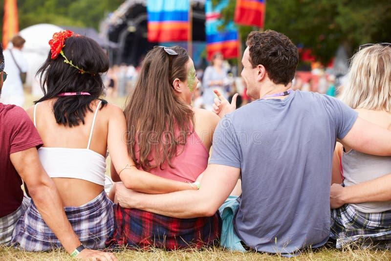 Νέοι που κάθονται υπαίθρια σε ένα φεστιβάλ μουσικής, πίσω άποψη στοκ εικόνα