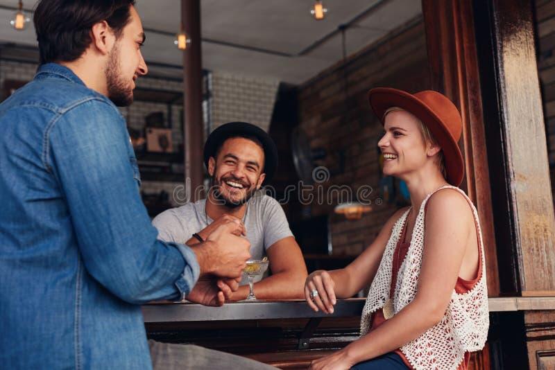 Νέοι που κρεμούν έξω σε έναν καφέ στοκ φωτογραφία