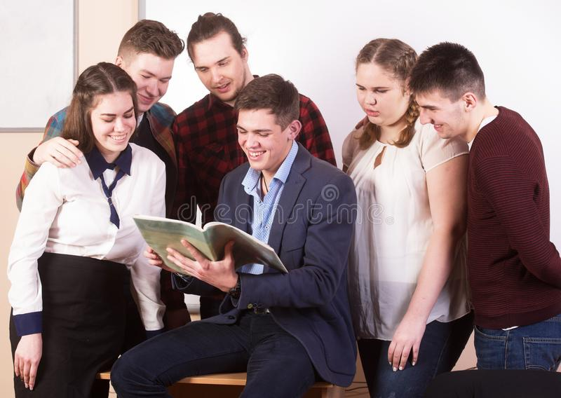 Νέοι που μελετούν με τα βιβλία στο άσπρο γραφείο στοκ φωτογραφία