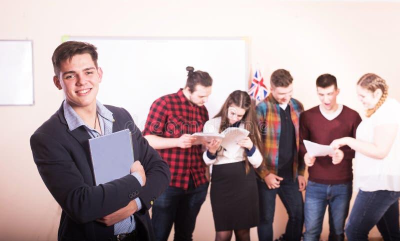 Νέοι που μελετούν με τα βιβλία στο άσπρο γραφείο στοκ εικόνες
