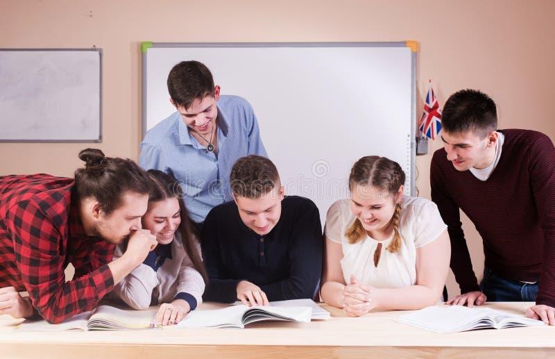 Νέοι που μελετούν με τα βιβλία στο άσπρο γραφείο στοκ εικόνα