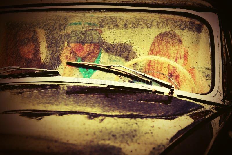 Νέοι που οδηγούν το εκλεκτής ποιότητας αυτοκίνητο στη βροχή στοκ φωτογραφία