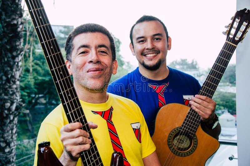 Νέοι που παίζουν τις κιθάρες με το φυσικό υπόβαθρο στοκ εικόνες με δικαίωμα ελεύθερης χρήσης