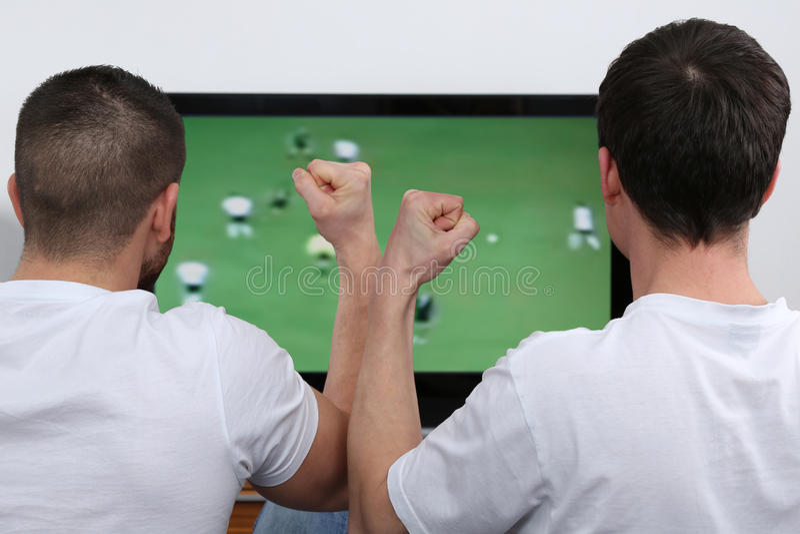 Νέοι που προσέχουν το ποδόσφαιρο στη TV στοκ εικόνες