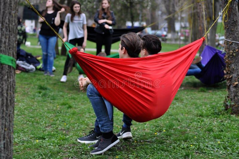 Νέοι που χαλαρώνουν στις αιώρες στο πάρκο στοκ φωτογραφίες με δικαίωμα ελεύθερης χρήσης