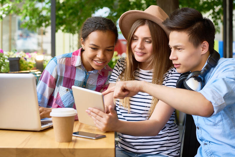 Νέοι που χρησιμοποιούν τις σύγχρονες συσκευές στον καφέ στοκ εικόνα με δικαίωμα ελεύθερης χρήσης