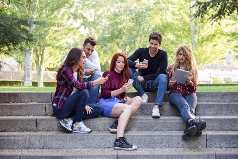 Νέοι που χρησιμοποιούν τους υπολογιστές smartphone και ταμπλετών υπαίθρια στοκ εικόνα με δικαίωμα ελεύθερης χρήσης