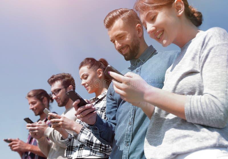 Νέοι που χρησιμοποιούν smartphones στο δίκτυο αναζήτησης στοκ φωτογραφία με δικαίωμα ελεύθερης χρήσης