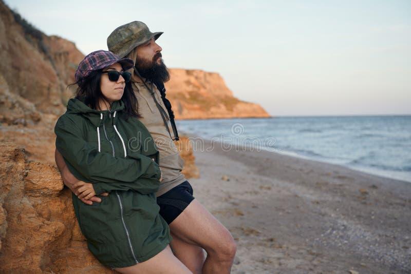 Νέοι ρομαντικοί ταξιδιώτες που εξετάζουν στον ουρανό παραλιών, που απολαμβάνει το ηλιοβασίλεμα τη θάλασσα - έννοια αγάπης, καλοκα στοκ φωτογραφία με δικαίωμα ελεύθερης χρήσης