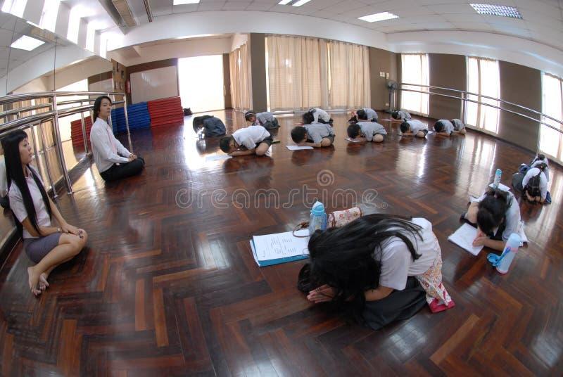 Νέοι σπουδαστές και φίλοι που μαθαίνουν πώς στον ταϊλανδικό χορό και με σεβασμό στοκ φωτογραφία με δικαίωμα ελεύθερης χρήσης