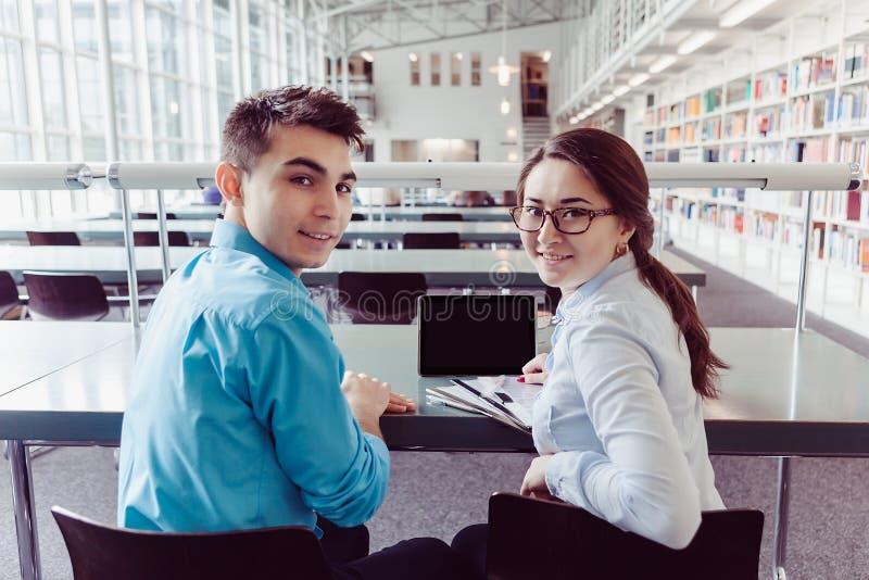 Νέοι σπουδαστές που μελετούν με το PC ταμπλετών στη βιβλιοθήκη στοκ φωτογραφίες
