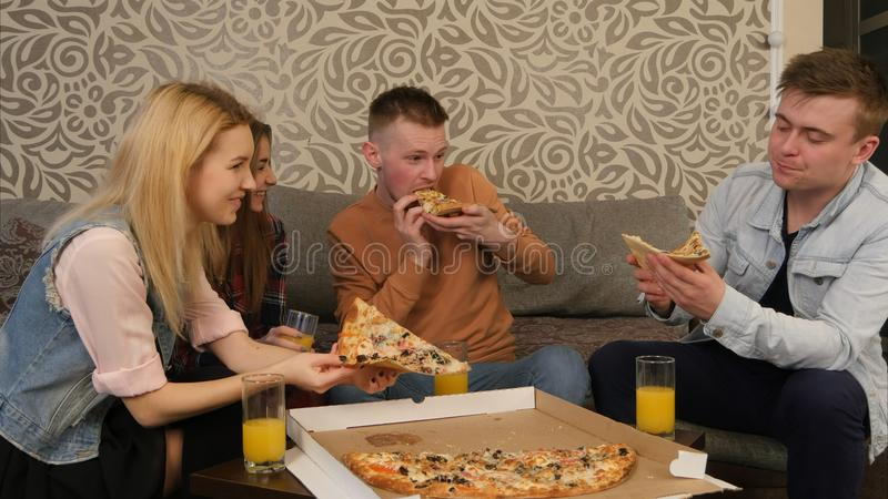 Νέοι στα περιστασιακά ενδύματα που τρώνε την πίτσα, ομιλία, γέλιο στοκ φωτογραφία με δικαίωμα ελεύθερης χρήσης
