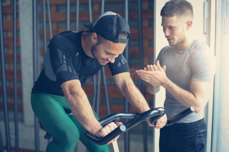 Νέοι στη γυμναστική Φίλοι workout στη γυμναστική και χρησιμοποίηση του έξυπνου τηλεφώνου στοκ φωτογραφία