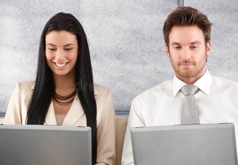 Νέοι συνάδελφοι που εργάζονται στο χαμόγελο lap-top στοκ εικόνες