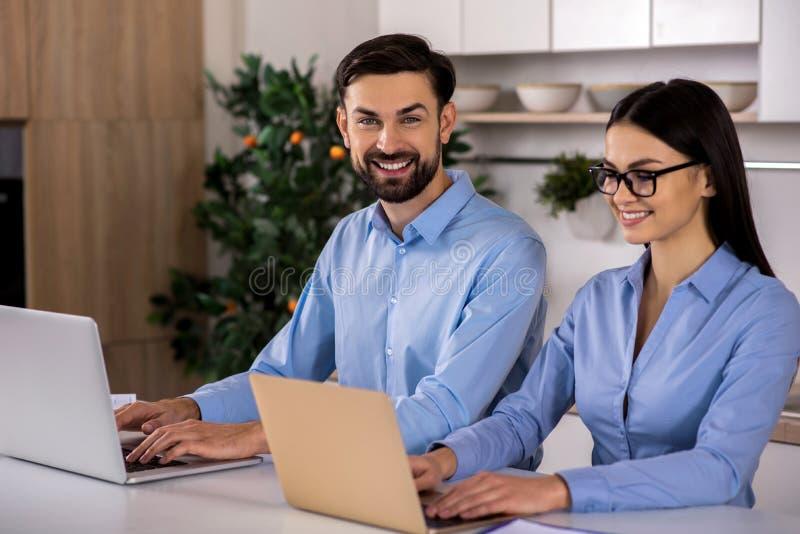Νέοι συνάδελφοι Smilign που χρησιμοποιούν τα lap-top τους στοκ εικόνες με δικαίωμα ελεύθερης χρήσης