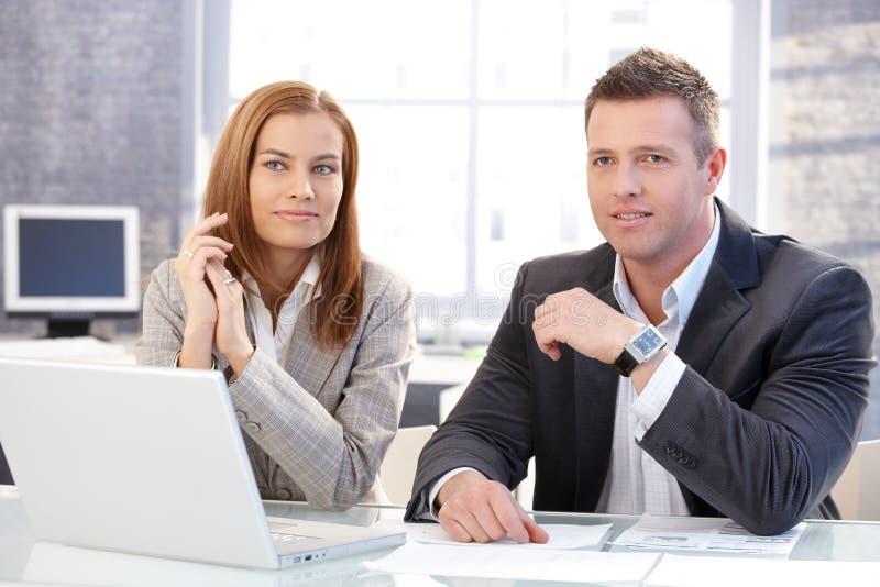 Νέοι συνάδελφοι που κάθονται στην εργασία γραφείων στοκ εικόνες