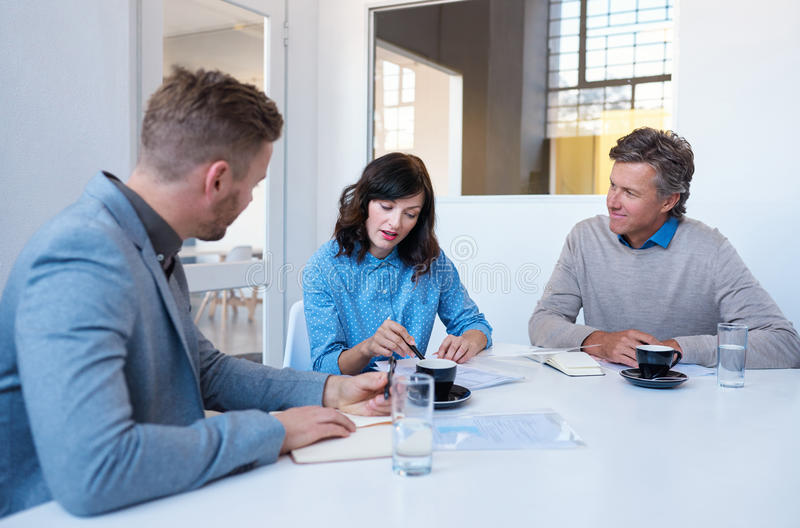 Νέοι συνάδελφοι που μιλούν μαζί σε μια αίθουσα συνεδριάσεων των γραφείων στοκ φωτογραφία