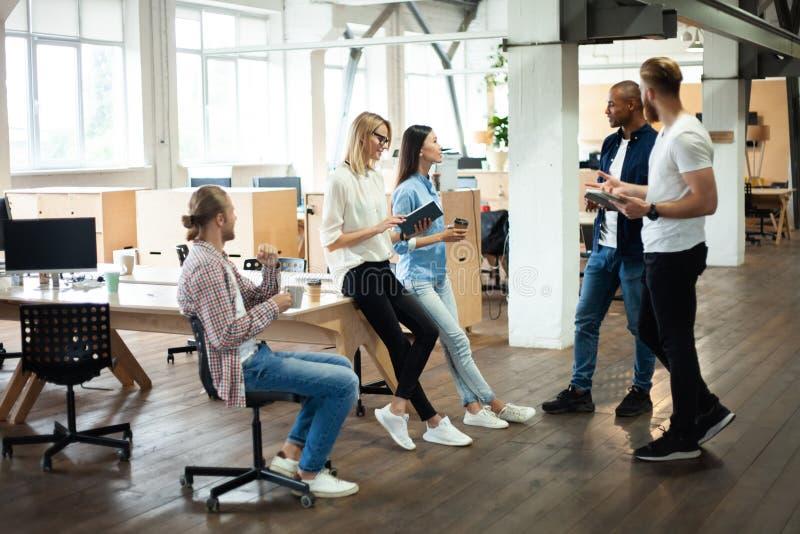 Νέοι σύγχρονοι συνάδελφοι στην έξυπνη περιστασιακή ένδυση που εργάζονται μαζί ενώ ξοδεύοντας χρόνος στο δημιουργικό γραφείο στοκ φωτογραφίες