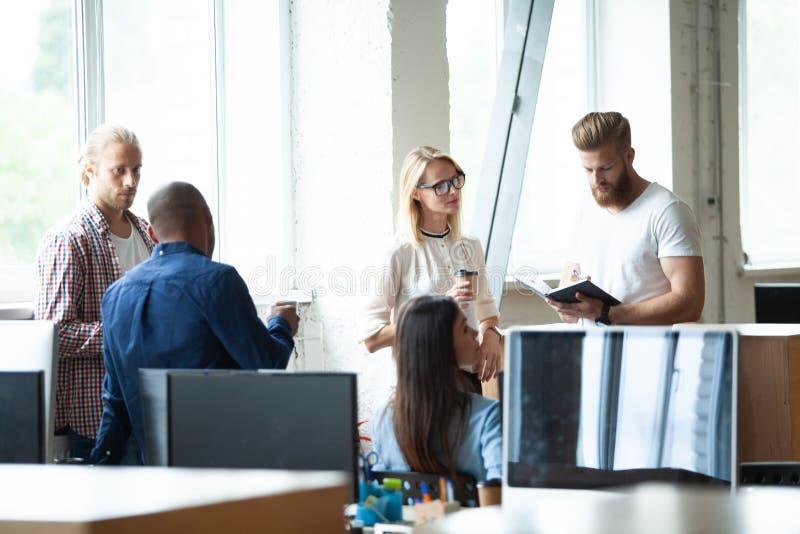 Νέοι σύγχρονοι συνάδελφοι στην έξυπνη περιστασιακή ένδυση που εργάζονται μαζί ενώ ξοδεύοντας χρόνος στο δημιουργικό γραφείο στοκ εικόνες