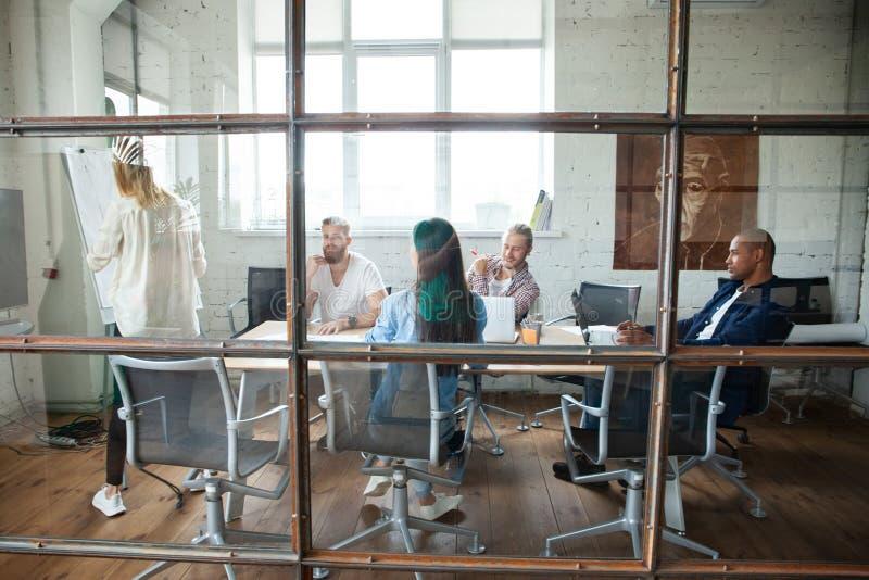 Νέοι σύγχρονοι συνάδελφοι στην έξυπνη περιστασιακή ένδυση που εργάζονται μαζί ενώ ξοδεύοντας χρόνος στο δημιουργικό γραφείο στοκ φωτογραφία