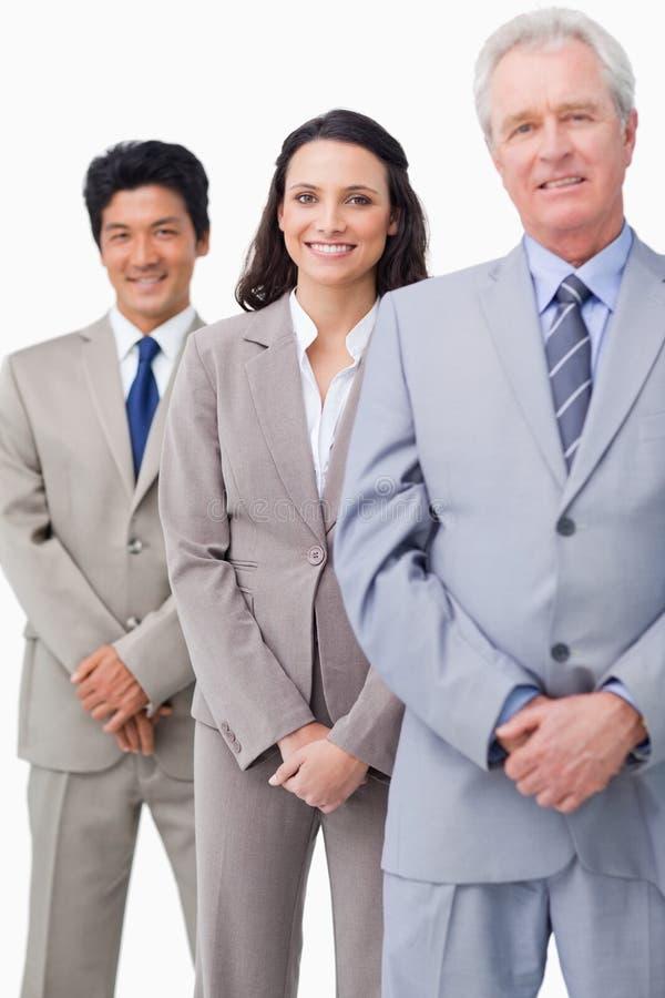 Νέοι υπάλληλοι που στέκονται πίσω από τον προϊστάμενό τους στοκ εικόνες