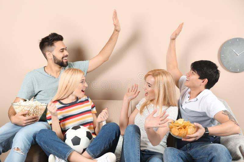 Νέοι φίλοι με τα πρόχειρα φαγητά που προσέχουν τη TV στον καναπέ στοκ εικόνα με δικαίωμα ελεύθερης χρήσης