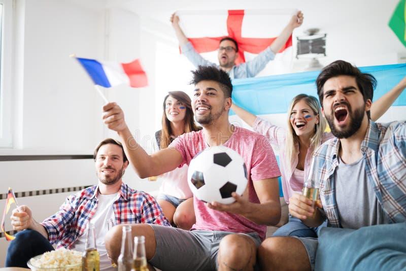 Νέοι φίλοι που προσέχουν τη TV και το ενθαρρυντικό ποδόσφαιρο στοκ εικόνα