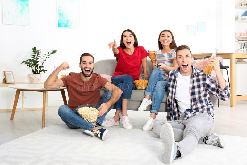Νέοι φίλοι που προσέχουν τη TV στο καθιστικό στοκ εικόνα