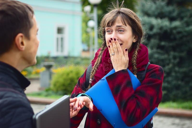 Νέοι φίλοι σπουδαστών που μιλούν στο κολλέγιο Το κορίτσι προσπαθεί να επιδείξει πώς ο σύζυγός της κήρυξε ερωτευμένος στοκ φωτογραφίες