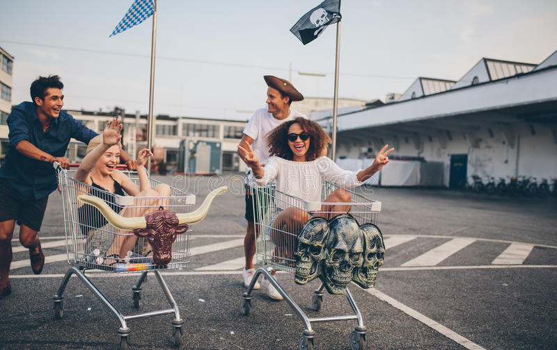 Νέοι φίλοι που έχουν τη διασκέδαση στα καροτσάκια αγορών στοκ εικόνα