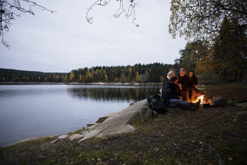 Νέοι φίλοι που κάθονται κοντά στη φωτιά από τη λίμνη στο σούρουπο στοκ εικόνα με δικαίωμα ελεύθερης χρήσης