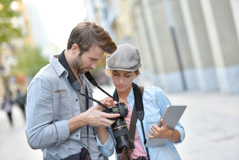 Νέοι φωτογράφοι που χρησιμοποιούν τη κάμερα και την ταμπλέτα στοκ εικόνα με δικαίωμα ελεύθερης χρήσης