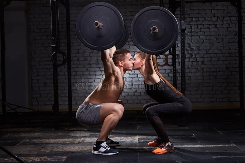 Νέοι όμορφοι αθλητικοί γυναίκα και άνδρας που φιλούν και που ανυψώνουν έναν αλτήρα από τις στάσεις οκλαδόν ενάντια στο τουβλότοιχ στοκ εικόνα
