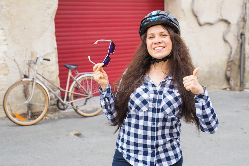 Νέοι όμορφοι αντίχειρες εκμετάλλευσης γυναικών επάνω και γυαλιά ηλίου στο ποδήλατο υποβάθρου και την κόκκινη πόρτα στοκ φωτογραφίες με δικαίωμα ελεύθερης χρήσης