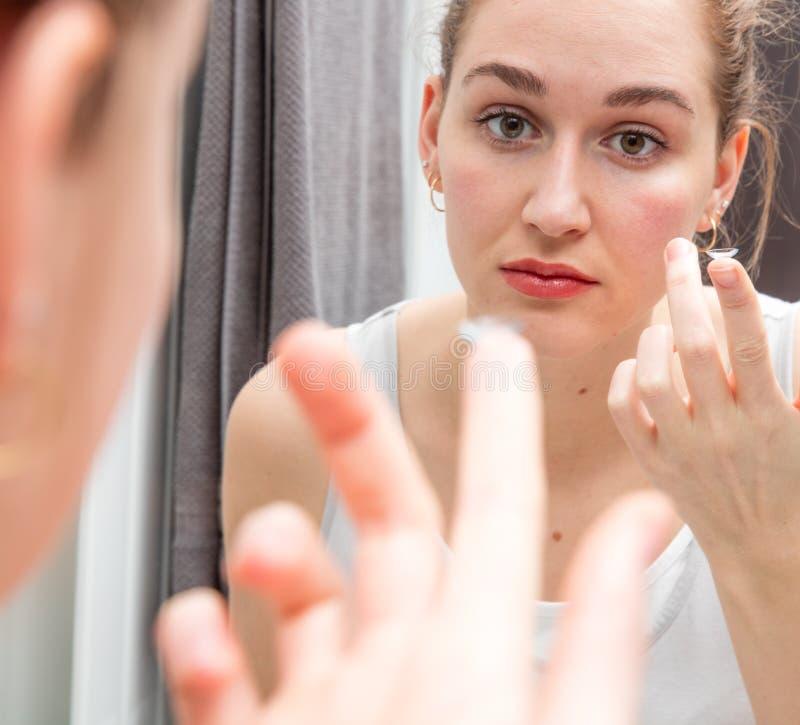 Νέοι όμορφοι μεταβαλλόμενοι φακοί επαφής γυναικών μπροστά από τον καθρέφτη στοκ εικόνα με δικαίωμα ελεύθερης χρήσης