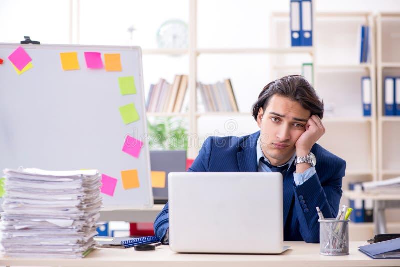 Νέος άνδρας υπάλληλος δυστυχισμένος με την υπερβολική εργασία στοκ φωτογραφία