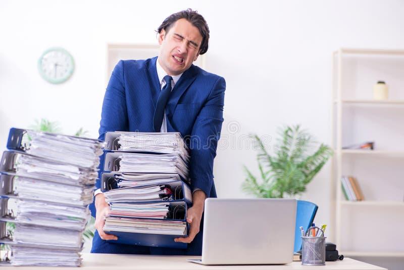 Νέος άνδρας υπάλληλος δυστυχισμένος με την υπερβολική εργασία στοκ φωτογραφίες