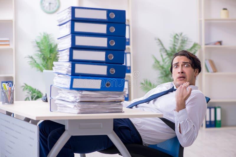 Νέος άνδρας υπάλληλος δυστυχισμένος με την υπερβολική εργασία στοκ εικόνα