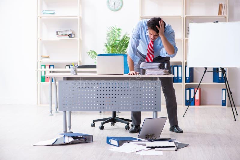 Νέος άνδρας υπάλληλος δυστυχισμένος με την υπερβολική εργασία στοκ εικόνες