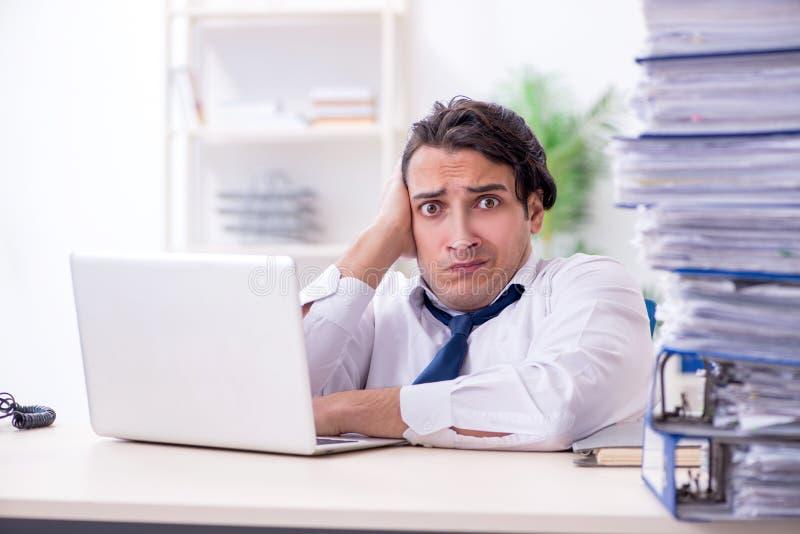Νέος άνδρας υπάλληλος δυστυχισμένος με την υπερβολική εργασία στοκ εικόνα με δικαίωμα ελεύθερης χρήσης