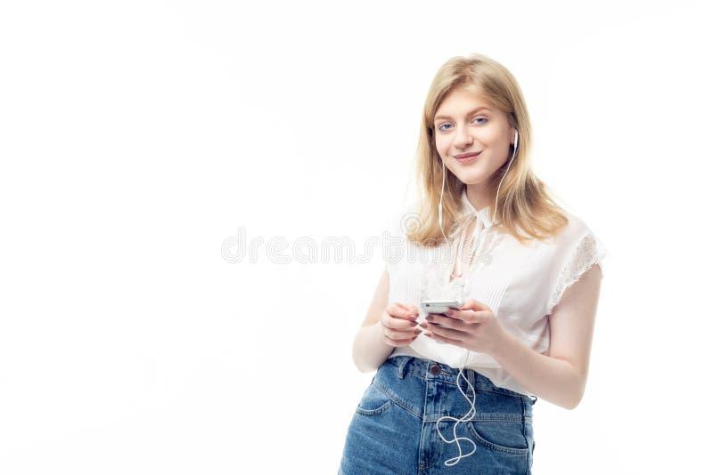 Νέος έφηβος που ακούει τη μουσική με το smartphone της στοκ εικόνα