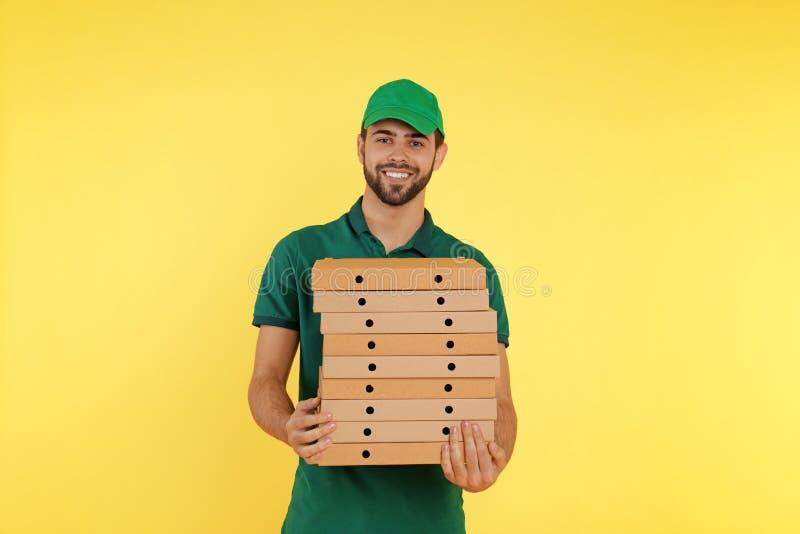 Νέος αγγελιαφόρος με τα κιβώτια πιτσών στο υπόβαθρο χρώματος στοκ φωτογραφία με δικαίωμα ελεύθερης χρήσης
