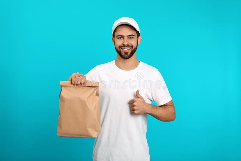 Νέος αγγελιαφόρος με την τσάντα εγγράφου στο υπόβαθρο χρώματος στοκ εικόνες με δικαίωμα ελεύθερης χρήσης