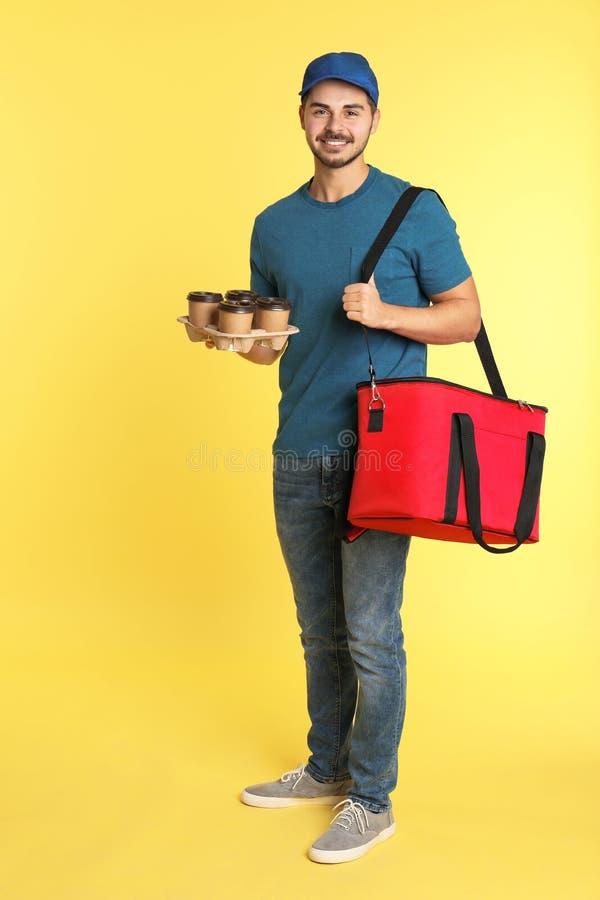 Νέος αγγελιαφόρος με τη θερμο τσάντα και ποτά στο υπόβαθρο χρώματος Παράδοση τροφίμων στοκ φωτογραφίες με δικαίωμα ελεύθερης χρήσης