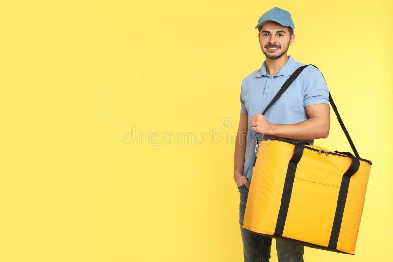 Νέος αγγελιαφόρος με τη θερμο τσάντα στο υπόβαθρο χρώματος, διάστημα για το κείμενο Παράδοση τροφίμων στοκ φωτογραφία