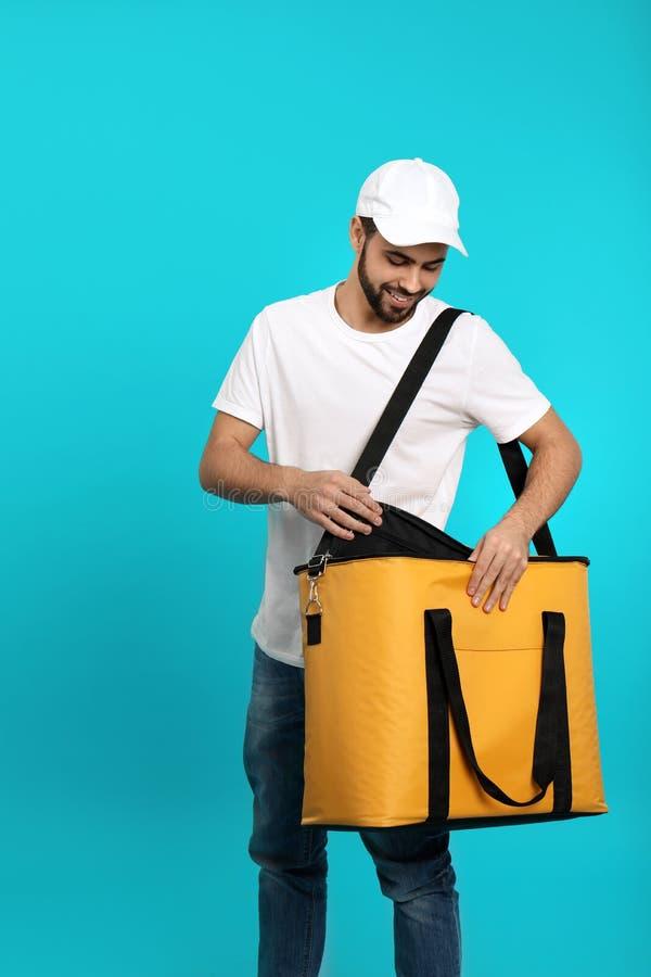 Νέος αγγελιαφόρος με τη θερμο τσάντα στο υπόβαθρο χρώματος Παράδοση τροφίμων στοκ φωτογραφίες
