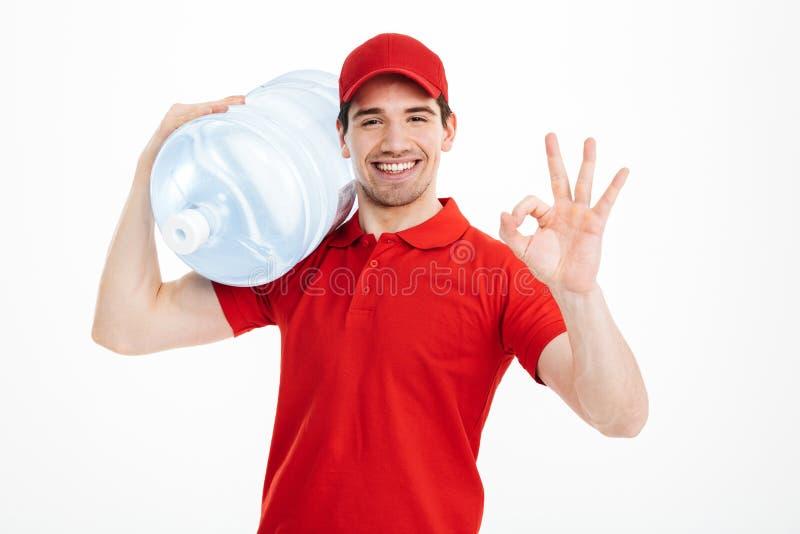 Νέος αγγελιαφόρος παράδοσης στο κόκκινο ομοιόμορφο μεταφέροντας μπουκάλι του fre στοκ εικόνες με δικαίωμα ελεύθερης χρήσης