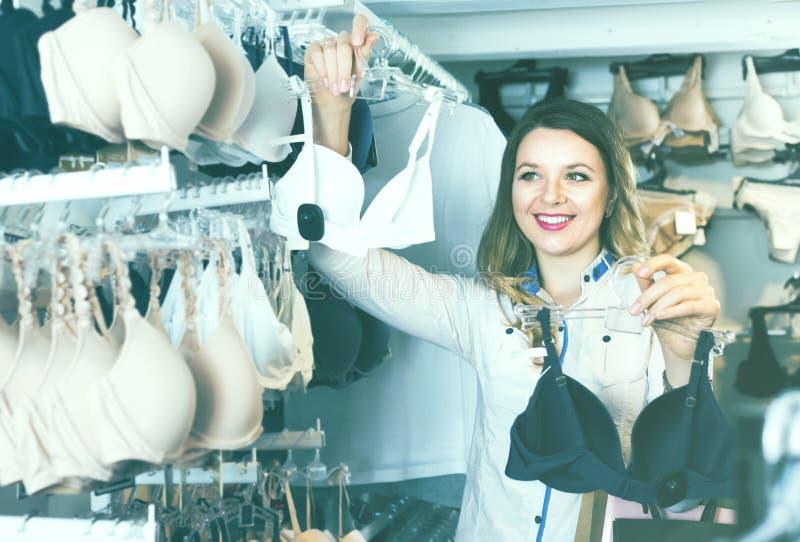 Νέος αγοραστής γυναικών που εξετάζει τους στηθοδέσμους στοκ εικόνα