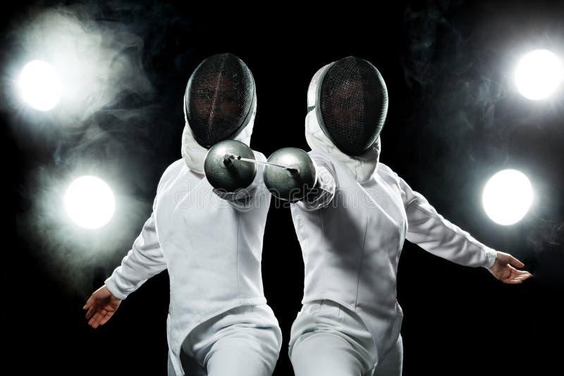 Νέος αθλητής ξιφομάχων που φορά τη μάσκα και το άσπρο περιφράζοντας κοστούμι κράτημα του ξίφους στο μαύρο υπόβαθρο με τα φω'τα στοκ εικόνες