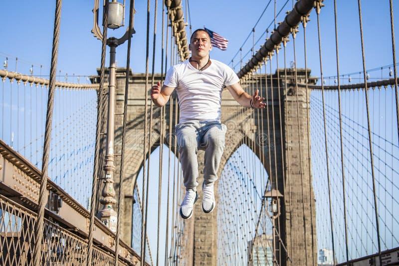 Νέος αθλητής που ασκεί και που πηδά στη γέφυρα του Μπρούκλιν στοκ φωτογραφία